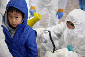 C54K15 Medical staff in protective gear check radiation levels on local residents in Koriyama, Fukushima prefecture.